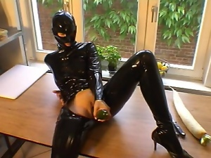 Fetish girl in rubber masturbating on table