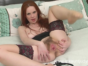 Mistique fingers her wet and hairy pussy.