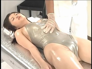 Shiny swimsuit on Japanese girl getting a massage