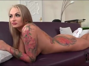 Tattooed blonde girl lies naked on the couch