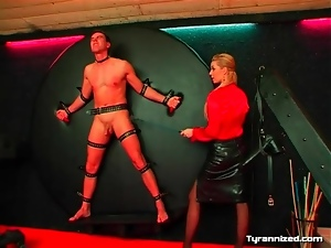 Man on the wheel of pain for leather skirt mistress