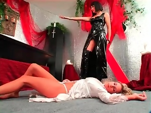 Blonde girl bound in coffin by latex mistress