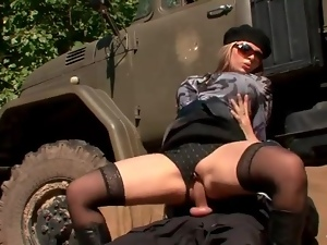 Classy clothed girl rides soldier cock outdoors