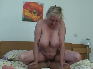 Blonde granny rides young cock happily.