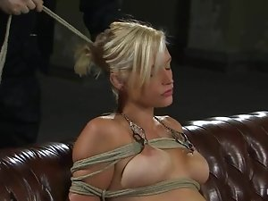 Tied up Lacey Jane sits on a sofa and gets toyed