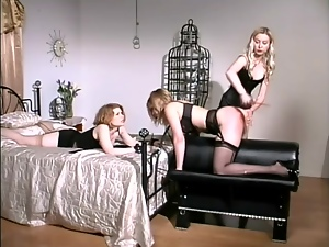 Three sexy bitches enjoy playing BDSM games in a bedroom