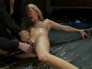Tied up blonde lies on the floor and gets toyed