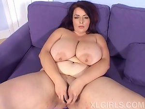 Big breasted MILF babe masturbates on the sofa