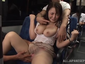 Busty Japanese milf gives a titjob to a stranger in a bus
