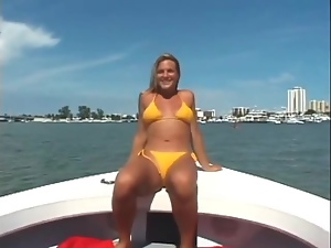 Blonde in yellow bikini models her pussy on a boat