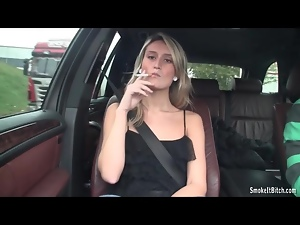 Sexy blonde smokes cigarette in the car