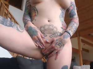 tattooed dark haired with ass plug exposes her extremely large tits on cam