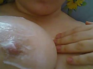 My slutty wife putting on lotion on her extremely large tits