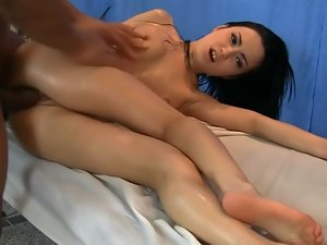 A ebony haired young lady is getting oiled up on the massage table