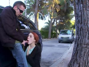 Redhead is stroking a prick in public by the car, just as she like sit